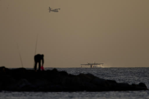 Foreign fire fighting planes load water from the Mediterranean sea off the coast near Netanya, Israel, Saturday, Nov. 26, 2016. More than 40 homes have been burned in a Jewish West Bank settlement and all 1,000-plus of its residents evacuated as firefighters continue battling blazes across the country for a fifth day. (AP Photo/Ariel Schalit)
