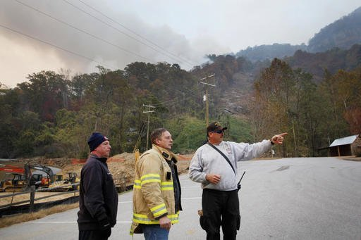 In a Saturday, Nov. 12, 2016 photo, from left, Stacey Graves, of Chapel Hill Fire Department, Steve West, of East Howellsville Fire Department, and Mack Cabe, of Orange Rural Fire Department, strategize how to protect a home near the fire in Chimney Rock, NC. North Carolina Gov. Pat McCrory on Monday planned update residents on wildfires in western North Carolina as officials report some progress in containing the blazes. (Angela Wilhelm/The Asheville Citizen-Times via AP)