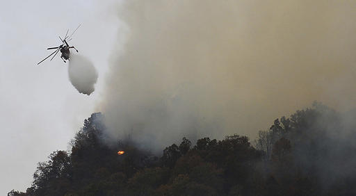 Crews work a wildfire near Lake Lure Friday, Nov. 11, 2016. State transportation officials say the wildfire near Lake Lure has forced the immediate closing of U.S. 64/74A and N.C. 9 in Rutherford County. (Patrick Sullivan/The Times-News via AP)