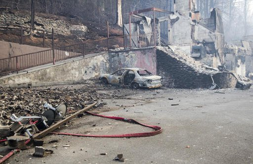 A scorched vehicle sits next to a burned out building in Gatlinburg, Tenn., Tuesday, Nov. 29, 2016. The fatal fires swept over the tourist town the night before, causing widespread damage. Thousands of people raced through a hell-like landscape to escape wildfires that killed several people and destroyed hundreds of homes in the Great Smoky Mountains. (AP Photo/Erik Schelzig)