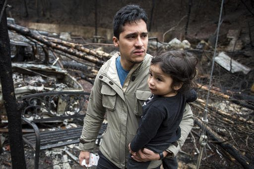 Allan Rivera holds onto his son Nathan Rivera, 23 months old, as he looks at the remains of their home for the first time Monday, Dec. 5, 2016, in Gatlinburg, Tenn. The family evacuated from their rental cabin before it was completely destroyed by a wildfire. A week ago on Monday, hurricane-force winds whipped up fires that killed over a dozen people and damaged or destroyed over a 1,000 buildings in the Great Smoky Mountains tourist region. (Andrew Nelles/The Tennessean via AP)
