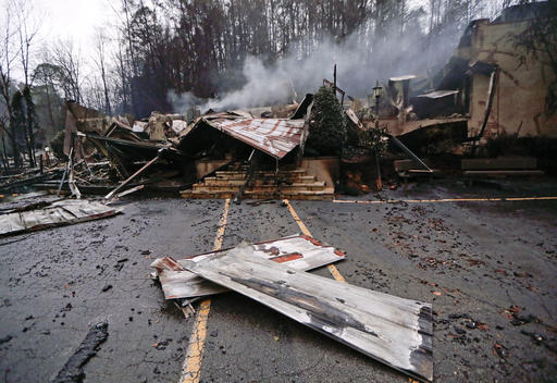 Smoke rises from the remains of the Alamo Steak House on Wednesday, Nov. 30, 2016, in Gatlinburg, Tenn., after a wildfire swept through the area Monday. Tornadoes that killed five people are adding to an onslaught of drought, flood and fire plaguing the South. The deadly overnight storms crashed into Alabama and Tennessee just as crews began to control wildfires around the resort town of Gatlinburg. (AP Photo/Mark Humphrey)
