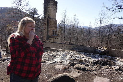 Tammy Sherrod views the remains of her home in the Roaring Fork neighborhood of Gatlinburg, Tenn., Friday, Dec. 2, 2016. Residents on Friday, were getting their first look at what remains of their homes and businesses in Gatlinburg, after a wildfire tore through the resort community on Monday, Nov. 28. (AP Photo/Adam Beam)