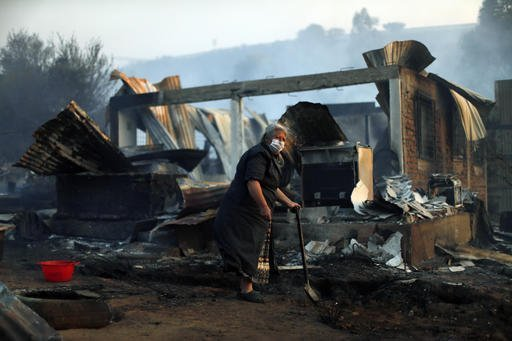 Nora Villarroel, 59, stand beside the remains of her burned house in Valparaiso, Chile, Monday, Jan. 2, 2017.  The fire, driven by strong winds, swept through forest land in the hills outside the Chilean port of Valparaiso, destroying dozens of homes, sending a pall of heavy smoke down onto the city and driving the authorities to evacuate hundreds of people. (AP Photo / Luis Hidalgo)