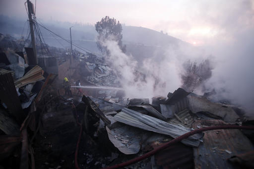 Firefighters work trying to control flames in Valparaiso, Chile, Monday, Jan. 2, 2017. The fire, driven by strong winds, swept through forest land in the hills outside the Chilean port of Valparaiso, destroying dozens of homes, sending a pall of heavy smoke down onto the city and driving the authorities to evacuate hundreds of people. (AP Photo/Luis Hidalgo)