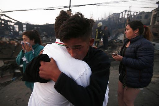 Two men hug each other during a fire in Valparaiso, Chile, Monday, Jan. 2, 2017. The fire, driven by strong winds, swept through forest land in the hills outside the Chilean port of Valparaiso, destroying dozens of homes, sending a pall of heavy smoke down onto the city and driving the authorities to evacuate hundreds of people. (AP Photo/Luis Hidalgo)