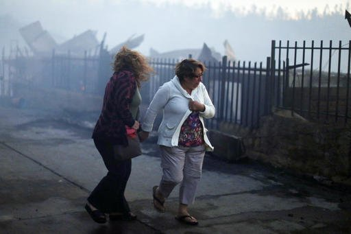 Women hold hands as they walk along remains of houses after a fire in Valparaiso, Chile, Monday, Jan. 2, 2017. The fire, driven by strong winds, swept through forest land in the hills outside the Chilean port of Valparaiso, destroying dozens of homes, sending a pall of heavy smoke down onto the city and driving the authorities to evacuate hundreds of people. (AP Photo/Luis Hidalgo)