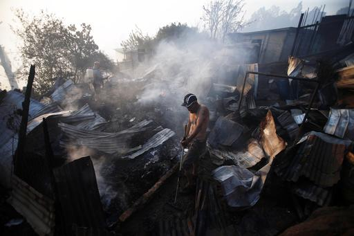 A man stands outside the remains of his home after flames destroyed it during a fire in Valparaiso, Chile, Monday, Jan. 2, 2017. The fire, driven by strong winds, swept through forest land in the hills outside the Chilean port of Valparaiso, destroying dozens of homes, sending a pall of heavy smoke down onto the city and driving the authorities to evacuate hundreds of people. (AP Photo/Luis Hidalgo)