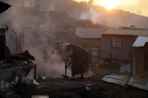 Nora Villarroel, 59, tries to put out the fire in the remains of her burned house in Valparaiso, Chile, Monday, Jan.  2, 2017. The fire, driven by strong winds, swept through forest land in the hills outside the Chilean port of Valparaiso, destroying dozens of homes and sending a pall of heavy smoke down onto the city. (AP Photo/Luis Hidalgo)