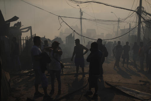 A group of people stand outside their homes due to a fire in Valparaiso, Chile, Monday, Jan. 2, 2017. The fire, driven by strong winds, swept through forest land in the hills outside the Chilean port of Valparaiso, destroying dozens of homes and sending a pall of heavy smoke down onto the city. (AP Photo/Luis Hidalgo)