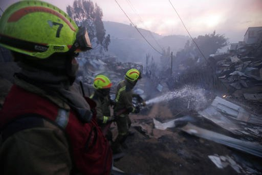 Firefighters work trying to control flames in Valparaiso, Chile, Monday, Jan. 2, 2017. The fire, driven by strong winds, swept through forest land in the hills outside the Chilean port of Valparaiso, destroying dozens of homes and sending a pall of heavy smoke down onto the city. (AP Photo/Luis Hidalgo)