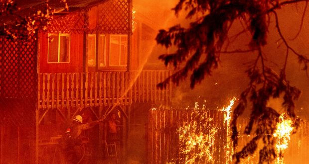 Firefighters battle burning structure at Dixie Fire