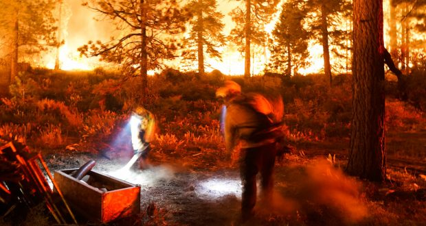 Two firefighters create a fuel break as the Caldor Fire burns near homes