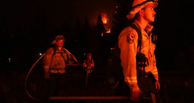Firefighters bathed in the light of the Caldor Fire
